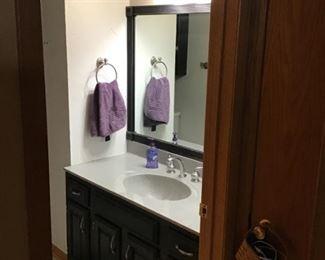 Bathroom vanity, mirror, light fixture, towel rack.