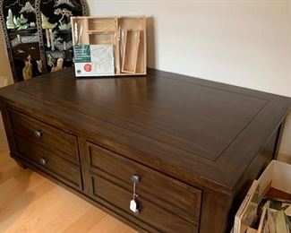 an Ethan Allen coffee table with ample storage drawers