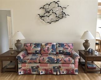 Geometric Patterned Sofa, Oak End Tables and Lamps.  Above is a metal work sculpture of flying birds