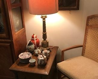 end table with vintage asian decorator pieces and one of a pair of mid century regency lamps