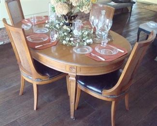 Vintage table with extra leaves and six leather seat chairs. (four chairs shown).