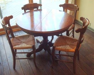 Vintage pedestal table with one leaf and six rush seat chairs.  ( four chairs shown).
