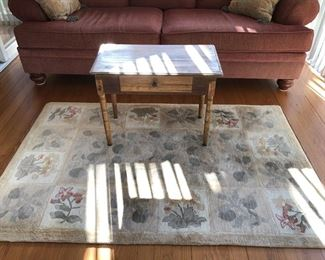 Botanical area Rug, Cranberry Sofa and Antique table