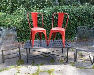 wrought iron chairs; metal table (glass top not shown), red metal chairs from France