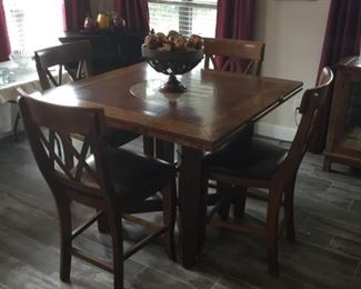 Breakfast table that turned into three different shapes. This is a squar table with 4 barstools. Or you can have 6 barstool. Also has a marble  lazy  Sue in the middle.  ( table & barstools will not go half price)