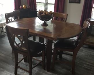 Breakfast table that turned into three different shapes. This is a oval table with 4 barstools. Or you can have 6 barstool. Also has a marble  lazy  Sue in the middle.  ( table & barstools will not go half price)