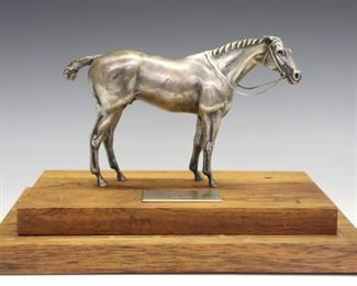 "Adalin Wichman, American, 1922-2013.  A 20th century Sterling Silver figure of the 18th century British Racehorse, Eclipse. Inscribed on underside of horse ""Adalin Wichman, Sterling, 53/100"" mounted on a stepped Rosewood base which is further inscribed ""53/100, Hand Made, Solid Rosewood, Adalin Wichman, 1972"".  Approx. 37.50 troy ozs Sterling. Some surface wear on figure, fading to base.  Base measures 11"" wide x 7"" deep with a glass cover 8 1/4"" high overall.  ESTIMATE $1,500-2,500"