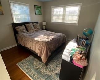 Full size bed with leather frame, area rug, small dresser, all furnishings for sale BED AND CREDENZA 250$