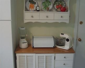 """Kitchen:  Vintage coffee pots top ceramic vegetable plates on a three-drawer wall shelf.  Below is a white cabinet (40-l/2"""" wide x 15-l/2"""" deep x 32"""" tall) which displays an OSTERIZER blender, metal bread box, and a SUNBEAM MixMaster with two beaters and two glass bowls."""