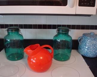 Kitchen: Two large green glass MILLS BAKER 4-quart canisters are shown with the vintage red glass pitcher and a blue splatter ware pot with lid.