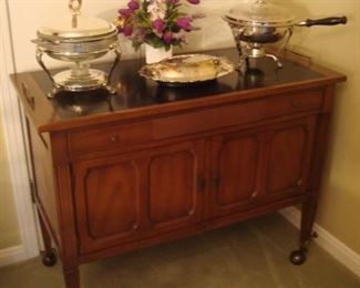 """Living Room: This server on casters has an attached black """"slate"""" top with handles; and there is one drawer over two doors.  It measures 40"""" wide x 19"""" deep x 31"""" tall.  The three silver-plate casseroles and floral arrangement are each priced separately."""