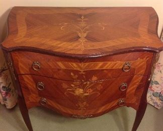 """Living Room:  This is a closer look at the small French-style three-drawer satinwood chest.  It has an inlaid design, brass drawer pulls, and brass decorative mounts on the corners.  It measures 27"""" wide at the back, 15-l/2"""" deep, and 28-l/2"""" tall."""