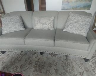 Grey sofa woth Nailheads and  tight back cushions. Comes with three pillows.  Custom sofa by England. Only 2 months old.
