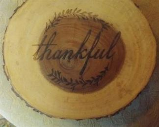 Thankful  written on slice of wood. on four legs. Hot plate.