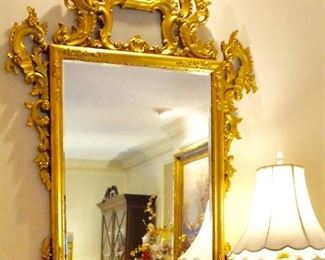 Ornately carved beveled gilded mirror