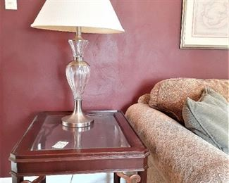 One of a pair of glass top mahogany vintage end tables with glass and silver tone contemporary lamp