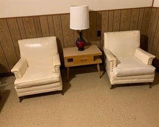 White vinyl side chairs. Blonde mid century modern end table. Set of iron and glass lamps