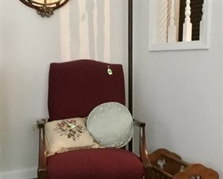 Burgundy chair with lovely floor lamp, magazine rack, with beautiful oval mirror.