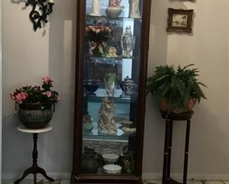 Lighted curio cabinet with 2 plant stands and lots of beautiful accessories in cabinet.