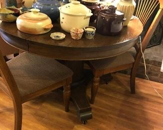 Lovely antique round dark oak table.  Also pictured is a great bean pot and pottery collection.
