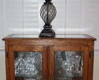 "Oak Frame Small Double Door Glass Credenza (30""H x 32""W x 14""D).  Show with Metal and Glass Table Lamp"