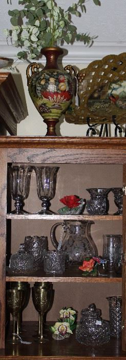 Exterior Cabinet of Entertainment Center showing contents of  Miscellaneous Crystal, Bisque Flowers and Brass Wine Glasses