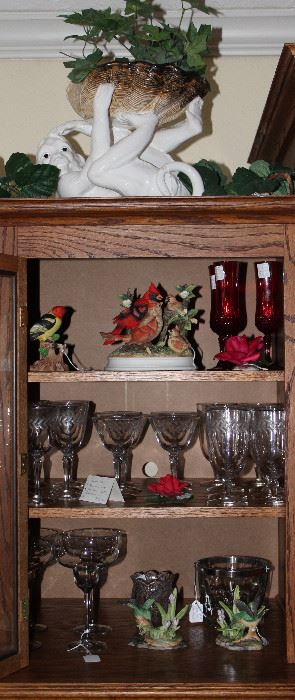 Exterior Cabinet of Entertainment Center showing contents of  Miscellaneous Crystal Stemware , Bisque Flowers and Bird Figurines