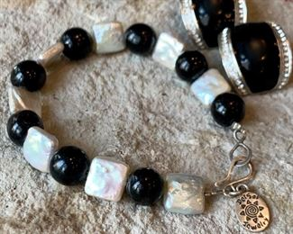 Mother of pearl bracelet by Del Sol Jewerly. $10. Clip on earrings black with faux diamonds. $8.