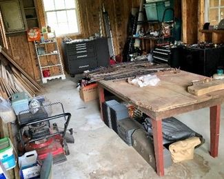 Another workshop, farm table, tool chest, push mower, tools boxes, plastic gun stocks and swords (on table)...