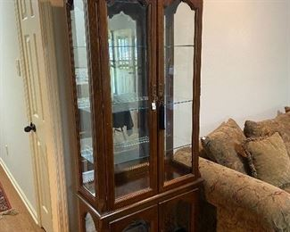 Lighted mirrored-back curio cabinet with glass shelves.