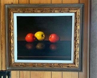 Realistic still life oil painting of apples in wood frame.