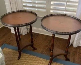 """SCHEDULE AN APPOINTMENT TO VIEW IN PERSON to view this pair of Baker leather-top side tables with brass gallery. They each measure 20"""" diameter, 28"""" high. The leather is embossed with three fleur-de-lis, which is visible in next photo. These are in excellent condition.  $1,100. Picture 1 of 2."""