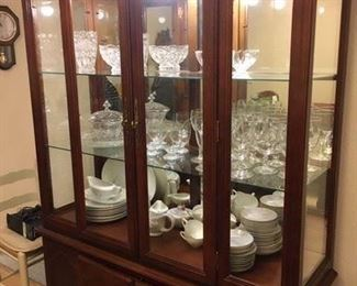 Lighted china hutch with glass shelving and mirrored back, lower cabinet storage