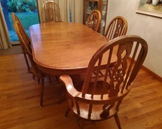 Solid oak dual pedestal dining table with 8 chairs 2 are captain chairs (excellent condition for your family gatherings large or small)