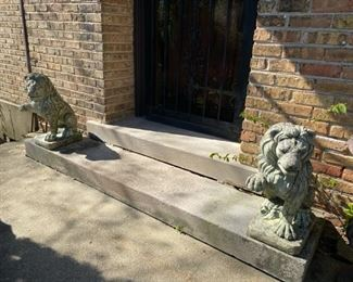 pair of concrete lions (one leg on each cracked)