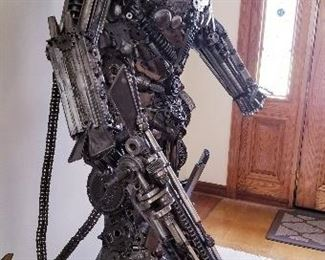 """LOT X- $22,000- Optimus Prime by Sculptor """" Mr. Santo"""" from Elena Bulatova Fine arts  (( Approximately 84""""  tall x 5 ft wide x 38 """" deep). This rendition is made out of recycled car and motorcycle parts. More info on artist can be found on https://www.elenabulatovafineart.com/mr-santo"""