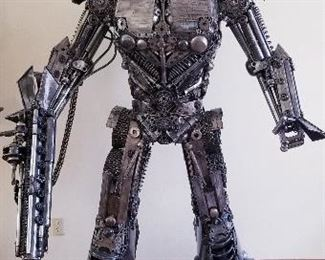 """LOT X- $22,000- Optimus Prime by Sculptor """" Mr. Santo"""" from Elena Bulatova Fine arts ( Approximately 84""""  tall x 5 ft wide x 38 """" deep). This rendition is made out of recycled car and motorcycle parts. More info on artist can be found on https://www.elenabulatovafineart.com/mr-santo"""