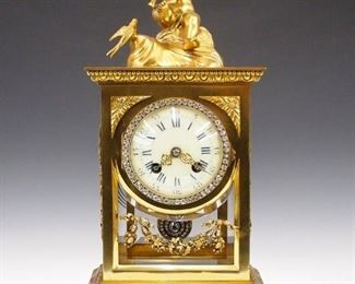 """An early 20th century French crystal regulator originally retailed by Tiffany & Co., New York.  8-day time and strike movement with porcelain dial and Roman numerals with fancy pierced hands and """"jeweled"""" bezel and pendulum.  Gilded bronze case with Green Onyx base, beveled glass panels and applied swags with foliage.  Slight wear, older repair to Onyx, running when cataloged.  15 1/2"""" high.  ESTIMATE $800-1,200"""