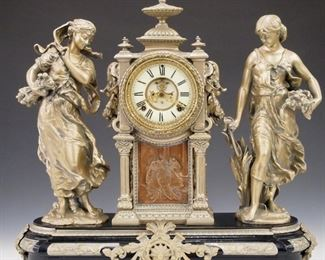 """A turn of the century Ansonia """"Summer and Winter"""" model figural clock.  8-day time and strike movement with two part porcelain dial and Roman numerals with visible escapement.  Cast Spelter case with double figures and central clock above a Bronze plaque.  Restored finish with minor wear, running when cataloged.  21"""" high.   ESTIMATE $1,500-2,500"""