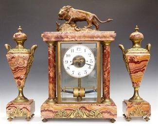 """A mid 1920's French Bulle """"Lion and Serpent"""" model three piece clock set.  Original electric movement with a Silvered dial and Arabic numerals in a gilded bezel.  Rouge marble case with four columns and beveled glass panels, surmounted by a Bronze Lion signed """"Ch. Aubert"""" and decorated with cast bronze capitols and fittings.  Movement recently overhauled and running, fitted with a """"D"""" battery case under base.  Slight wear, older repair to one column.  19 3/4"""" high overall.  ESTIMATE $2,000-3,000   See page 64 of """"La Bulle - Clock"""" by Henry L. Belmont for a similar example.  A copy of the book accompanies this lot."""