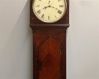"""A 19th century British Tavern clock.  8-day weight driven time and strike movement with painted iron dial, Roman numerals and subsidiary seconds bit.  Mahogany Gothic Revival style case with peak top, brass bezel and flat fluted detail, shaped lower door and rounded drop.   Case refinished with some wear, minor repair, some wear to dial, running when cataloged.  60 1/2"""" high.  ESTIMATE $1,000-2,000"""