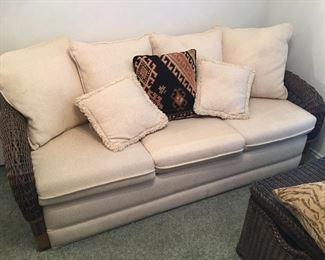 The futon is made with wicker back and side ends, beige upholstery, and back pillows.  In excellent condition.