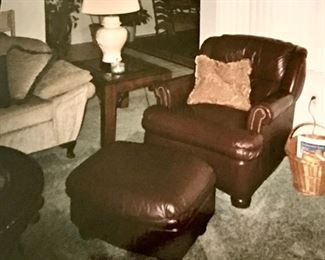 Brown leather nail-head chair with matching ottoman; lamp end table with a glass top; ginger jar lamp; and a vintage-chic sofa with rounded, relaxed arms.