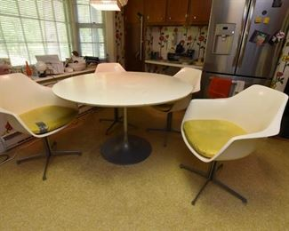 """Item 4: White Kitchen Table & Chairs: $375      Unmarked tulip-style 48"""" table (presumed to be Burke). Has four chairs, marked Burke, Inc. Yellow vinyl seat cushions are in fair condition. Two have repairs made with duct tape (what else?). White (formica?) table top is worn."""