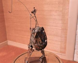Item 43: Brutalist rock sculpture $45 Abastract wire and metal form around rock.