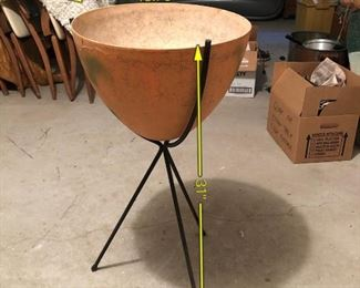 Item 53: Mid Century Bullet Planter  $75  The fiberglass pot has been painted orange and has green splotchy spray paint. Legs have some rust.