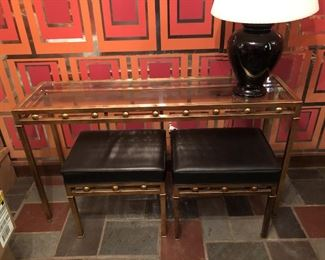 Item 55: Glass top metal table with two bench seats  $165  Glass is free of chips or cracks. Seats are upholstered in black vinyl with piping. One stool has four impressions in the vinyl as shown. Good condition.