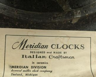 Item 58: Howard Miller for Meridian Wall Clock $295     Circa 1965, glazed ceramic, enameled aluminum. Signed with applied paper manufacturer's label to reverse: (Meridian Clocks Designed and Made by Italian Craftsmen in Ceramics Meridian Division Howard Miller Clock Company Zeeland, Michigan). One hand is missing, so repairs are needed.