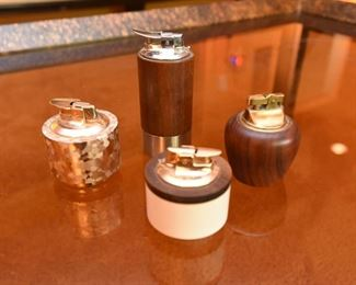 """Item 64: Collection of Four Lighters $50  Three Ronson:  The Norseman, Varaflame """"La Ronde,"""" and """"Luralite."""" The fourth is marked """"Genuine Teak"""""""