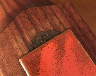 Item 63: Vintage Bovano Rosewood Lighter with Enamel on Copper details $15  One of the enameld copper panels has started to slide off of the glue. It isn't sticky, so it must have become too warm at some point. Unmarked lighter sits in top and needs to be reset with something to hold it in place.